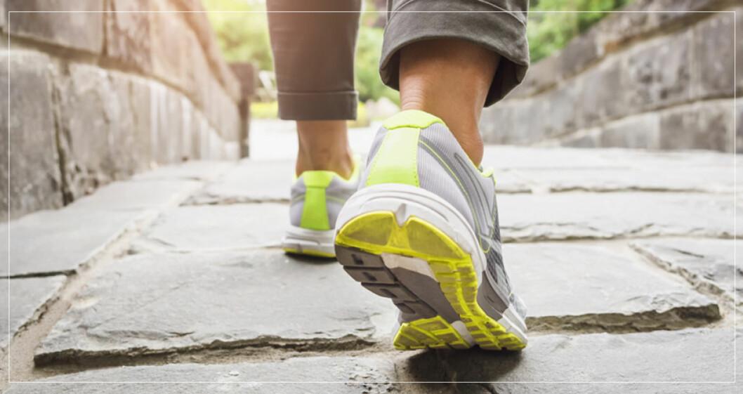 Promenadskor på fötter som går på stenväg.