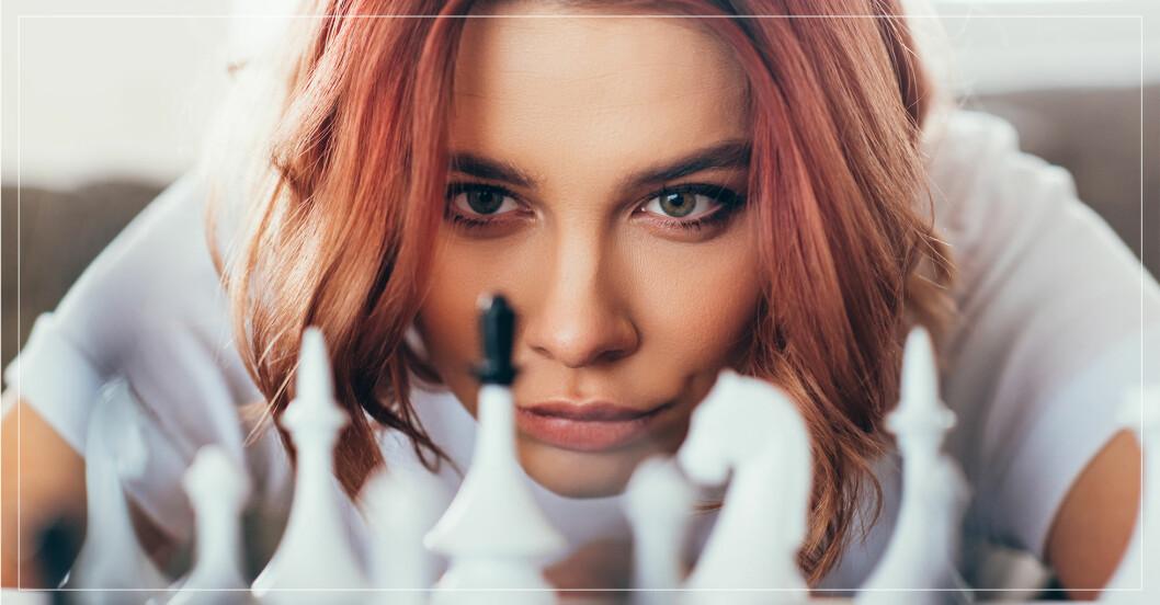 Rödhårig kvinna i 30-års åldern spelar schack.