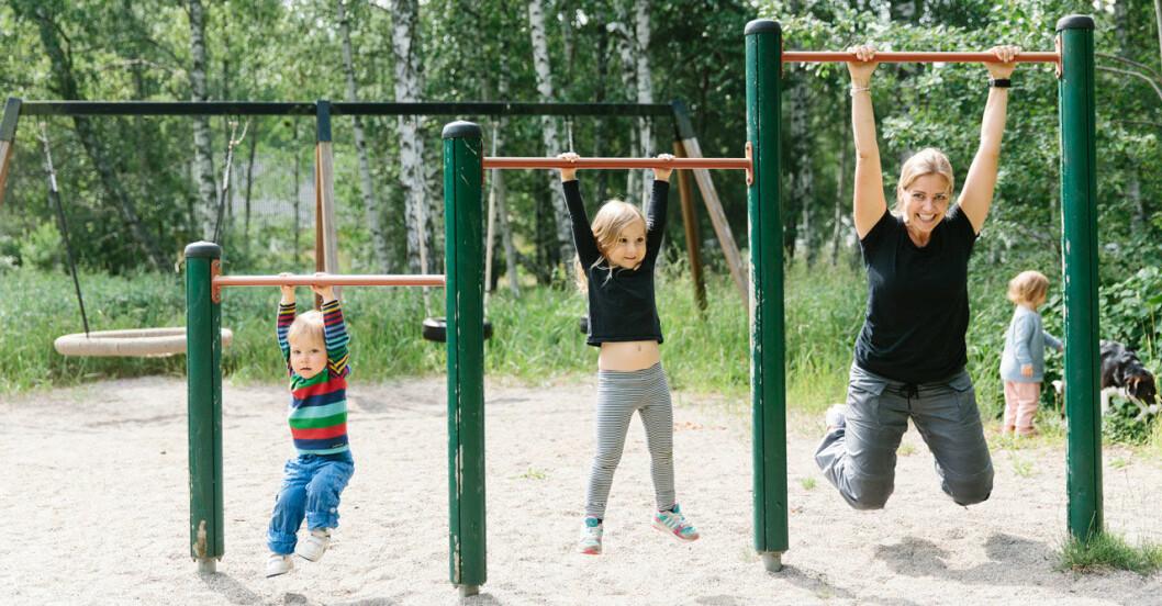 Mamma som tränar med sina barn i en lekpark