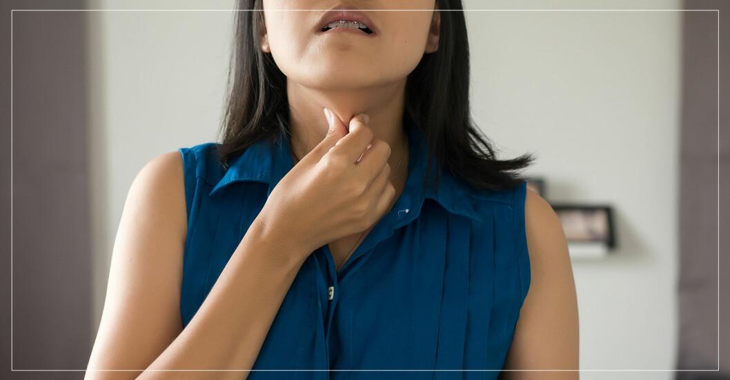 Kvinna som håller sig för halsen.