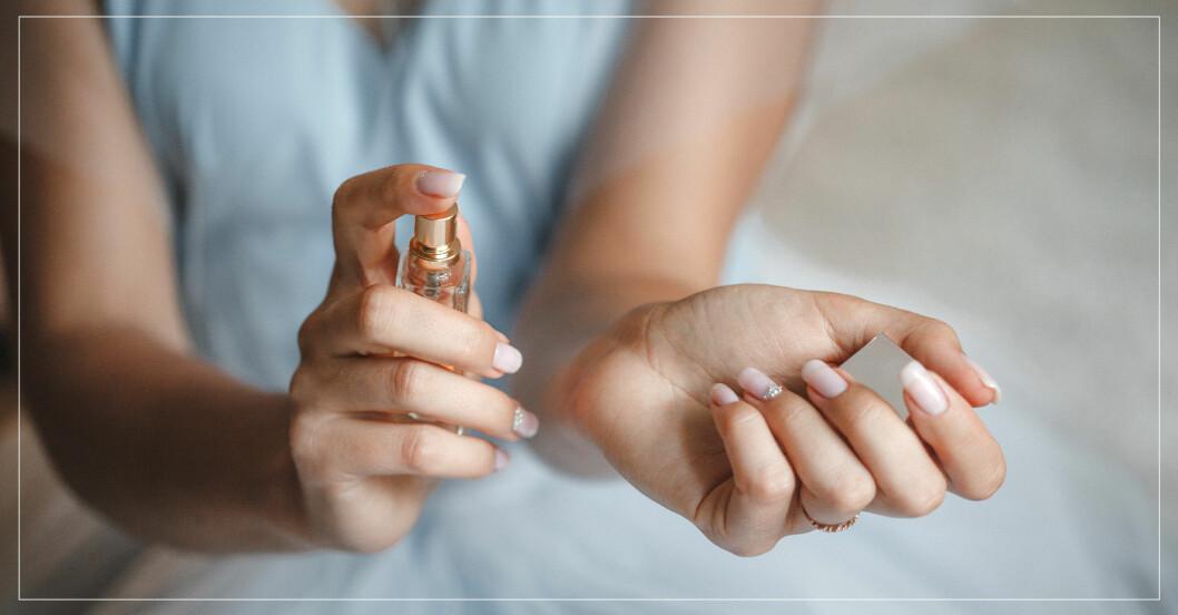 kvinna sprayar parfym på handleden