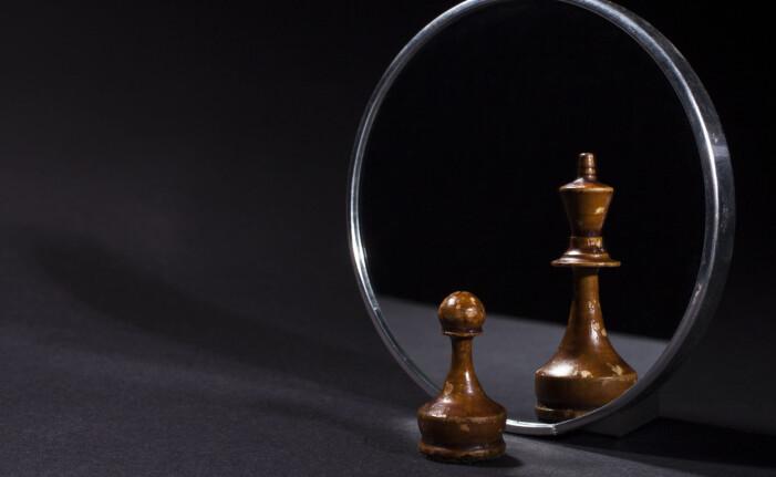 Schackpjäser som är olika stora framför spegeln och i spegelbilden.