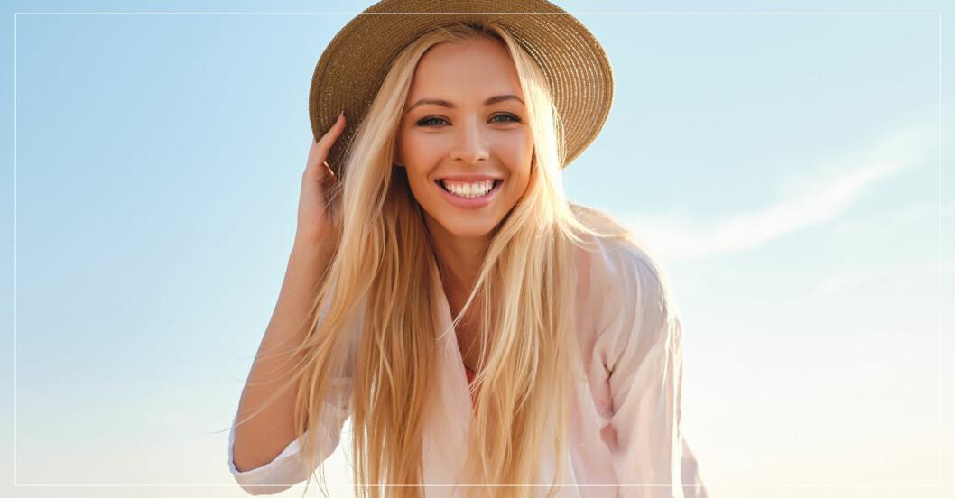 Kvinna med solhatt som ler under semestern
