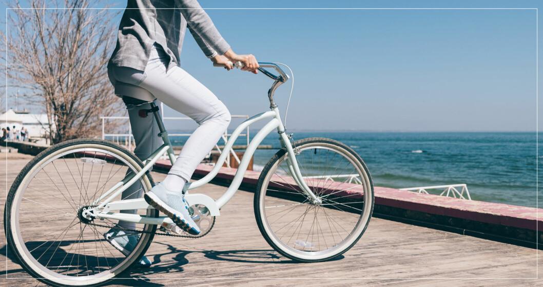 Kvinna på vit cykel vid vattenkanten.