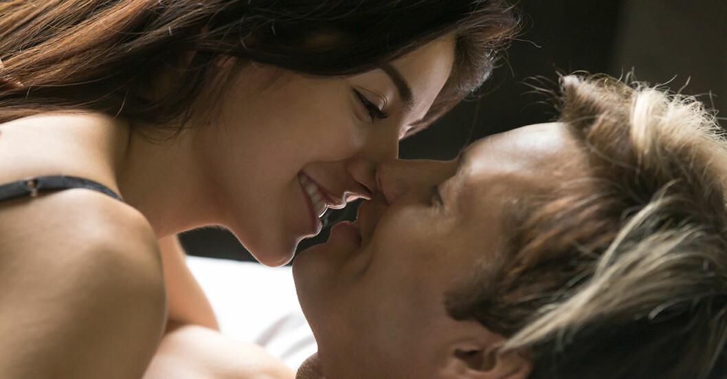 En kvinna och en man ligger i en säng och kysser varandra