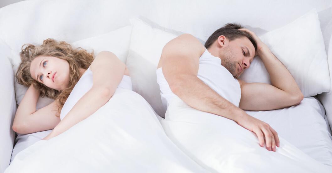 En kvinna och en man har inte sexlust utan ligger bortvända från varandra i en säng