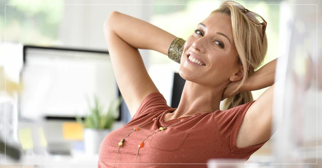 Kvinna som sitter tillbakalutad i stol med stort självförtroende