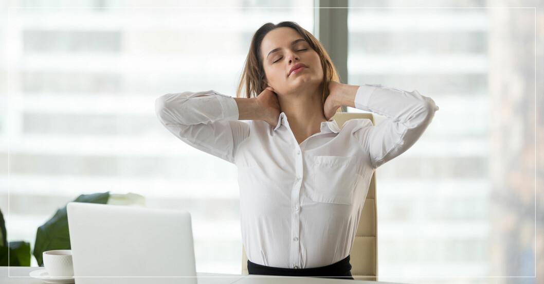 Kvinna som håller sig för nacken när hon sitter framför skrivbordet.
