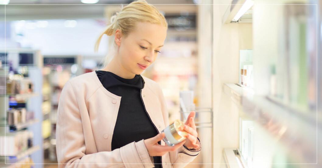 kvinna i sminkbutik läser texten på en burk