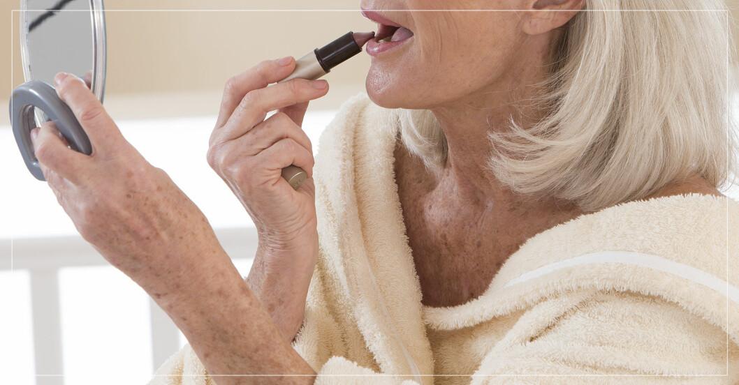 Kvinna som tar på sig läppstift.c