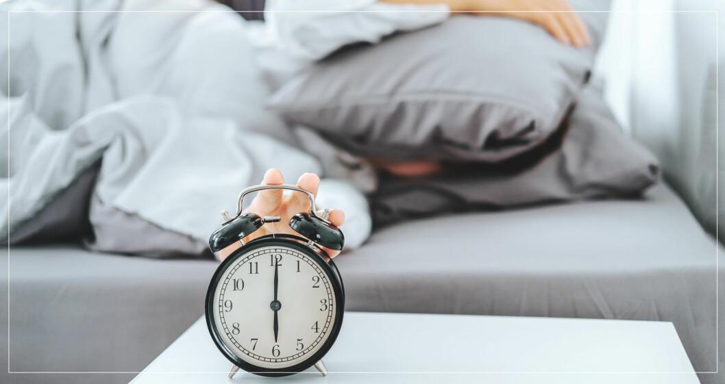 Kvinna sträcker sig efter väckarklocka för att snooza.