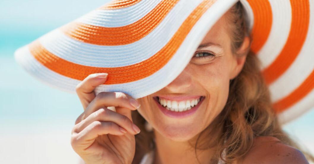 Kvinna på stranden med solhatt