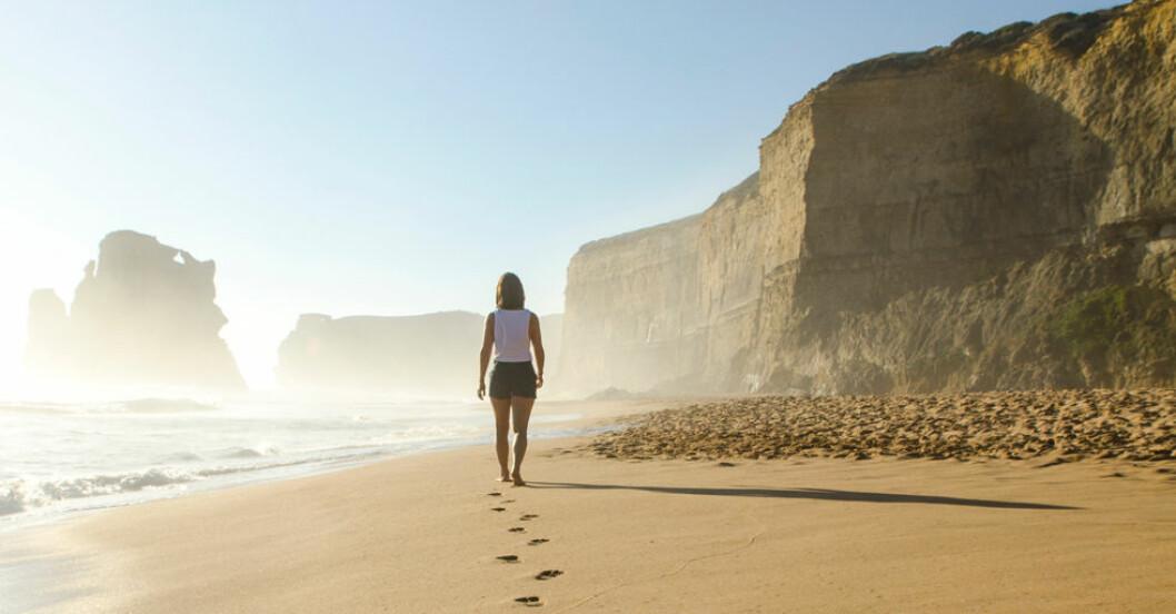 kvinna går på en solig sandstrand