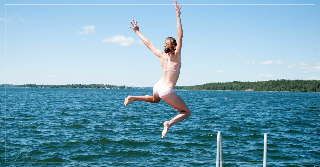 Kvinna badar och hoppar glatt ifrån brygga ned i vattnet.