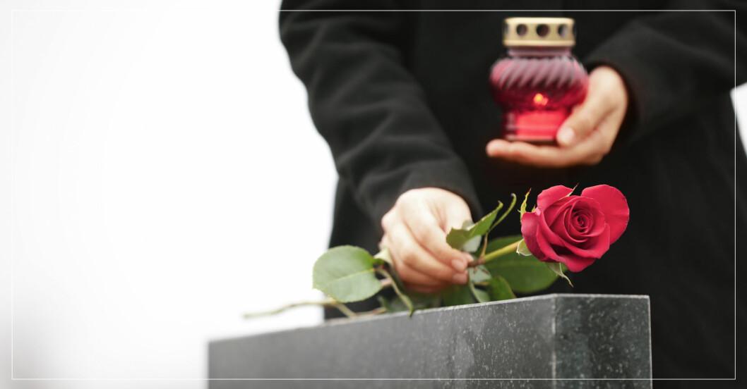 Sörjande kvinna lägger röd ros på gravsten och håller ljus i handen.