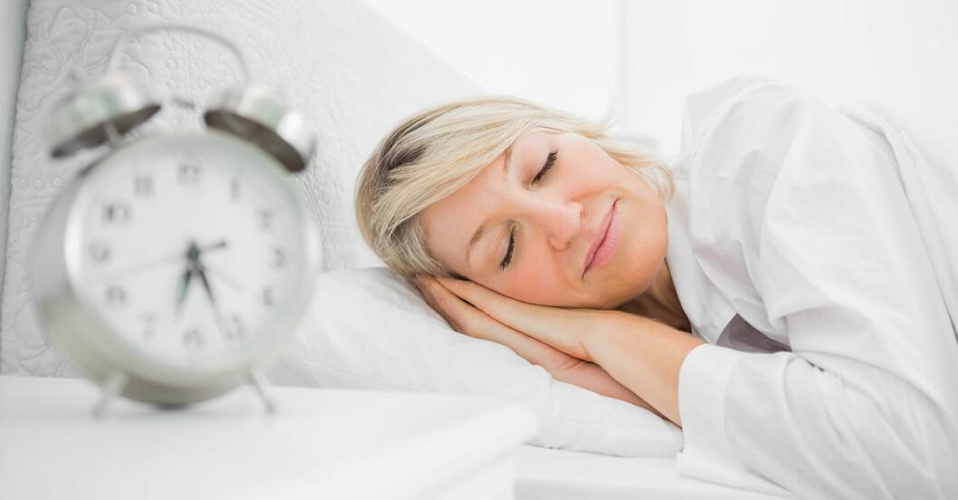 Väckarklocka i förgrunden och medelålders kvinna som sover i säng i bakgrunden