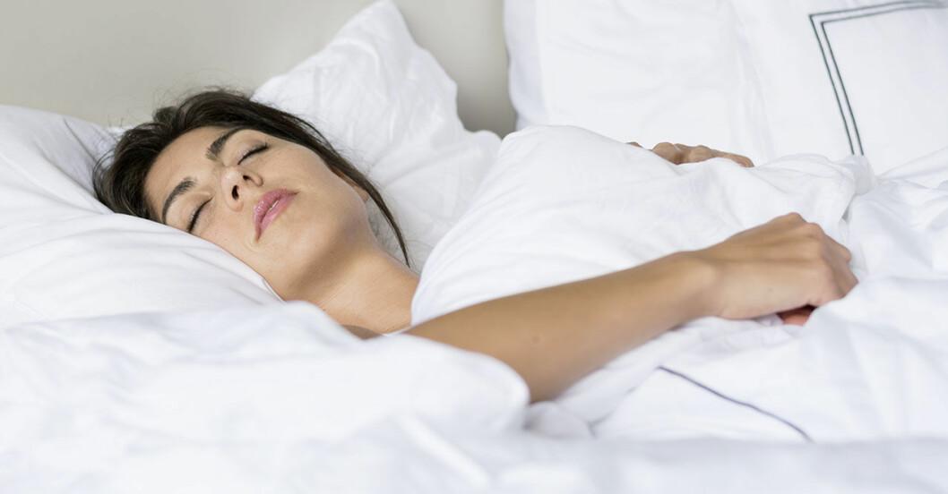 Kvinna sover på rygg i säng med vita sängkläder