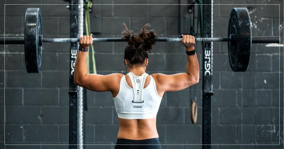Kvinna lyfter vikter iklädd sport-bh