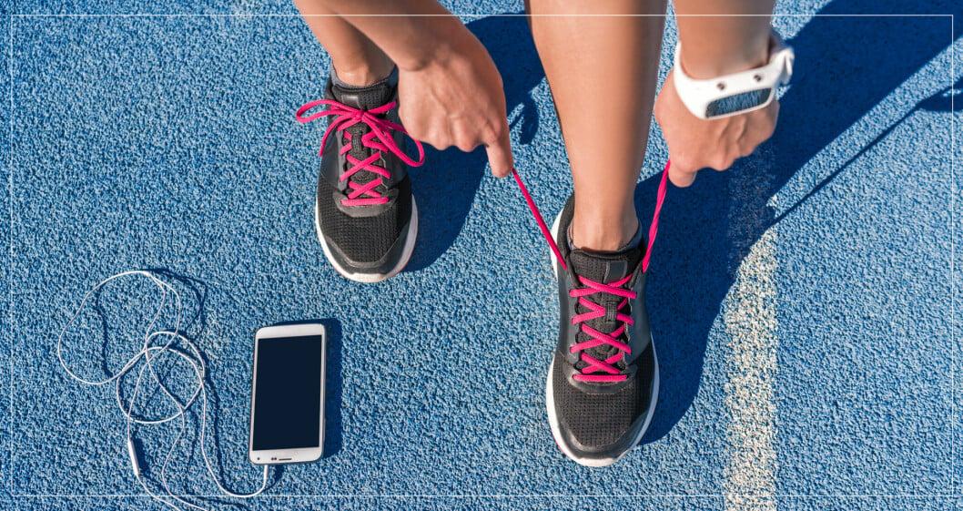 Kvinna som knyter skorna på en blå löparbana.