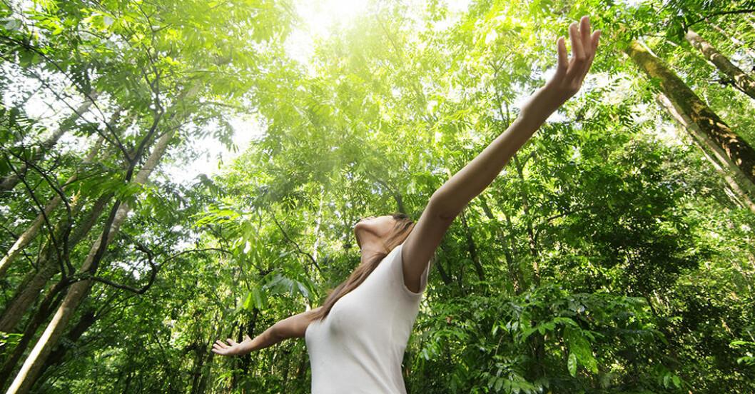 Kvinna återhämtar sig i naturen och sträcker på kroppen för att slappna av.