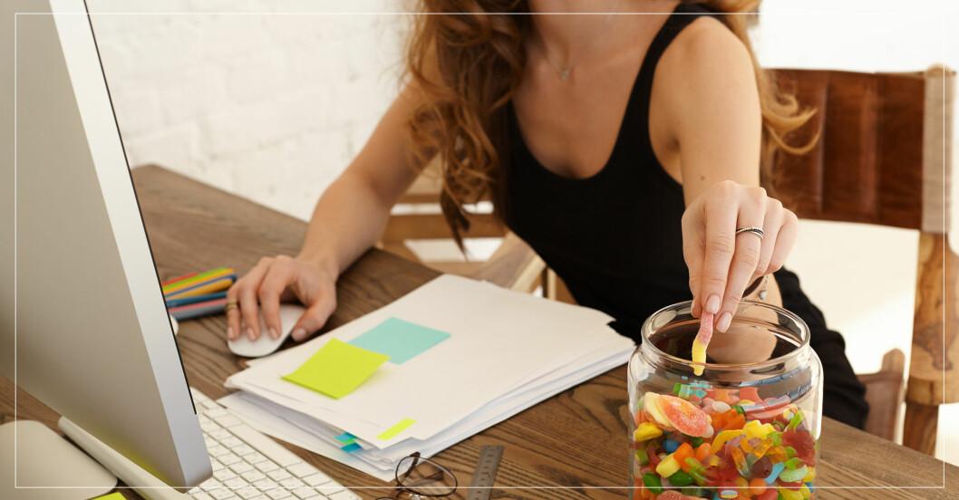 Kvinna framför dator äter godis på grund av stress