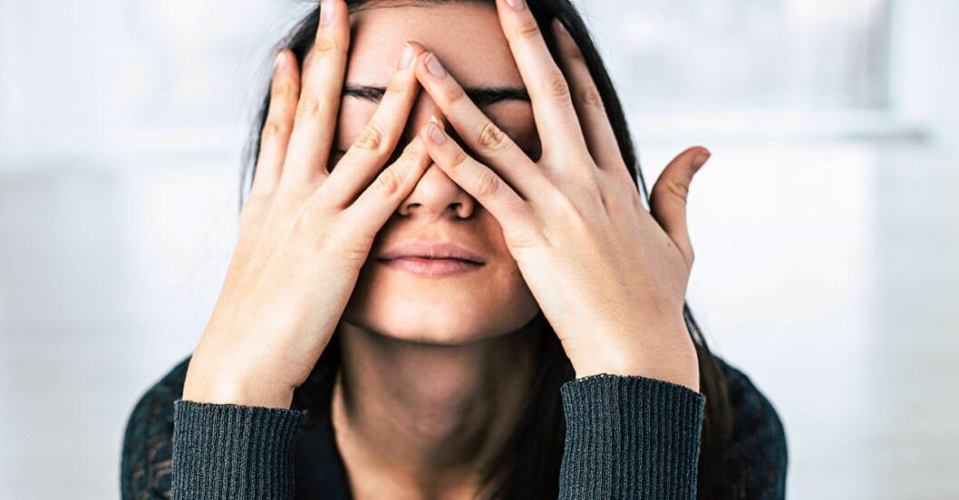 Stressad kvinna med mörkt hår håller händerna för ansiktet