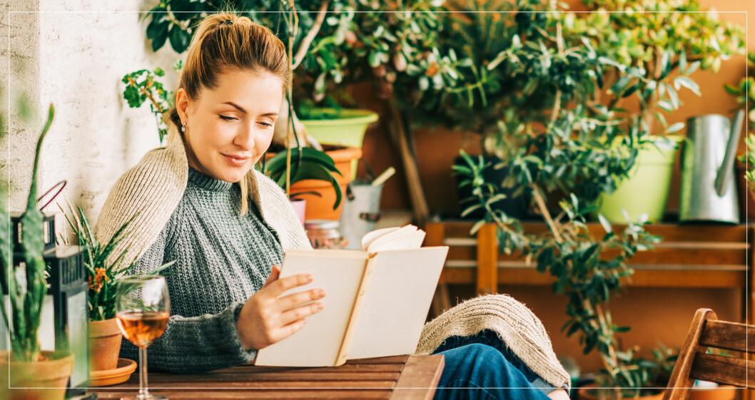 Kvinna som läser bok på sin balkong med ett glas vin.