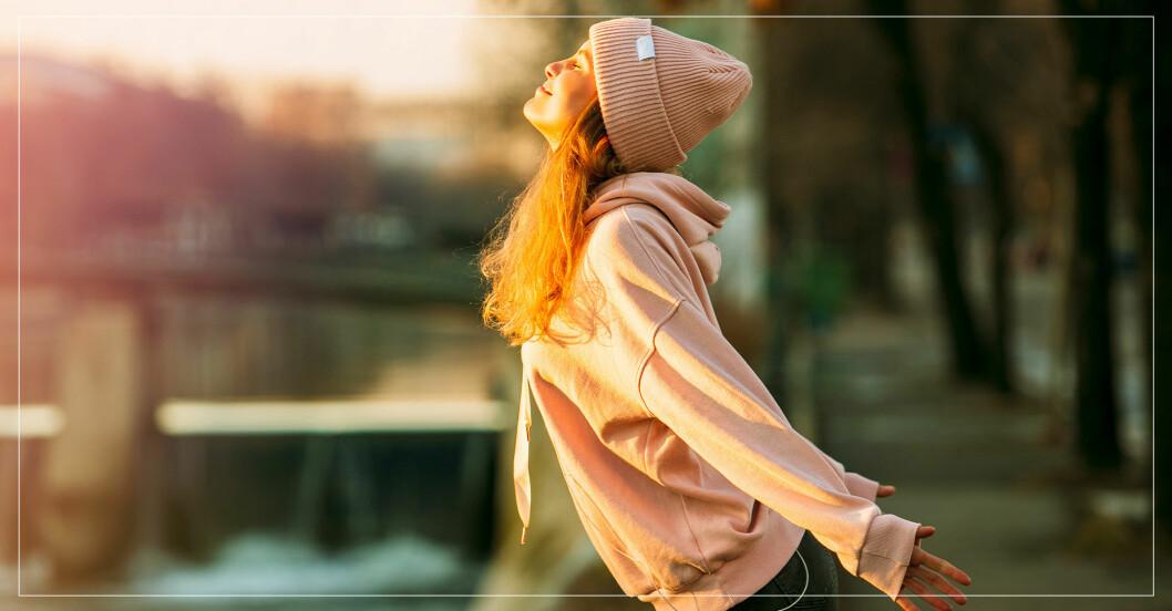 kvinna i park njuter av solstrålar i ansiktet