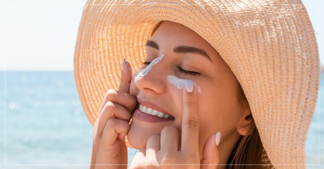 Kvinna i solhatt smörjer in ansiktet