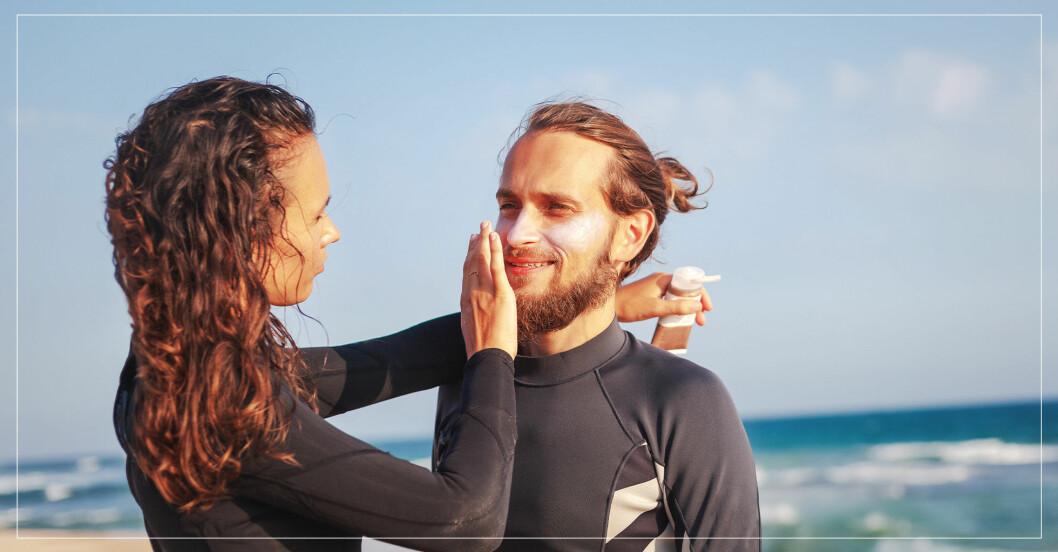 Kvinna smörjer in mans ansikte med solcreme