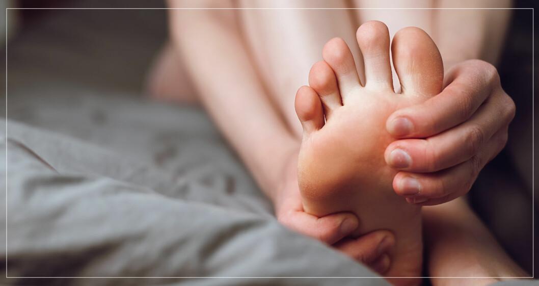 Kvinna masserar sin fot.