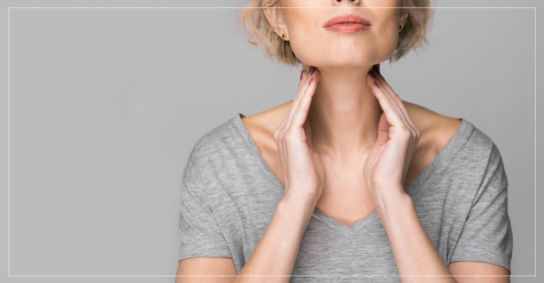 kvinna som håller sig på halsen