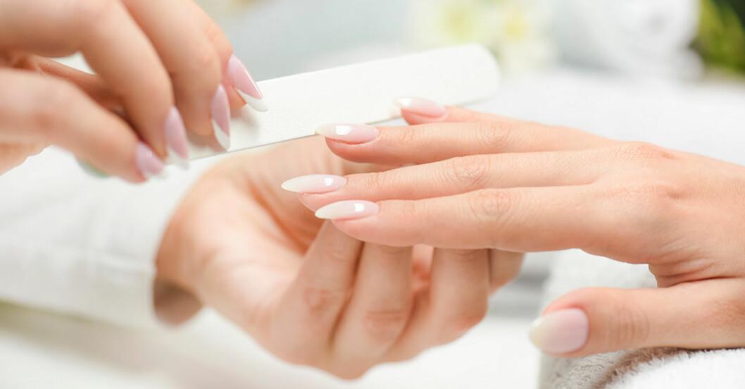 Kvinna får sina naglar filade genom manikyr