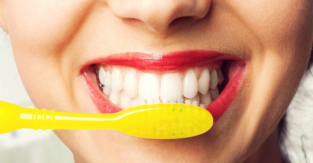 Kvinnas leende mun med gul tandborste.