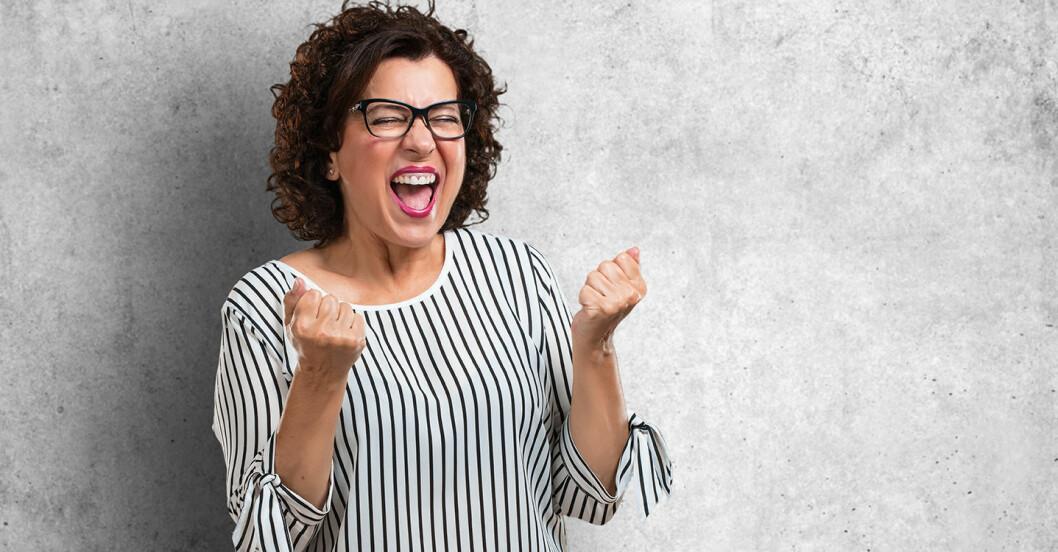 Kvinna med lockigt hår och glasögon knyter nävarna, kniper ihop ögonen och öppnar munnen.