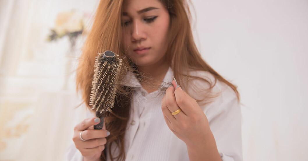 Kvinna som har tappar mycket hår när hon borstar.