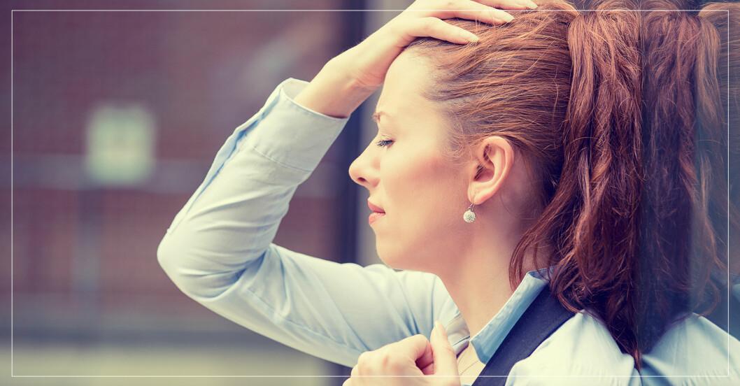 stressad kvinna som står lutad mot en vägg