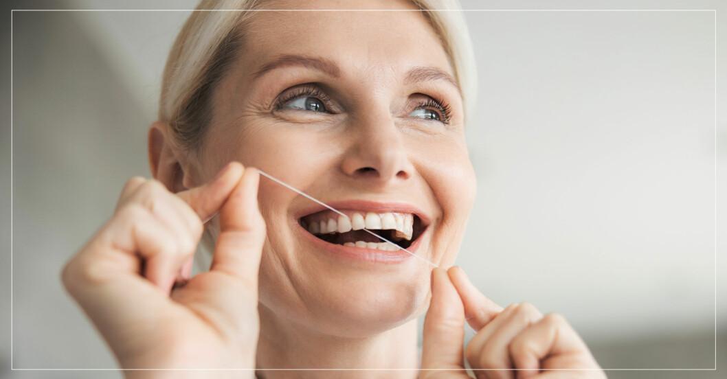 Kvinna gör rent mellan tänderna med tandtråd