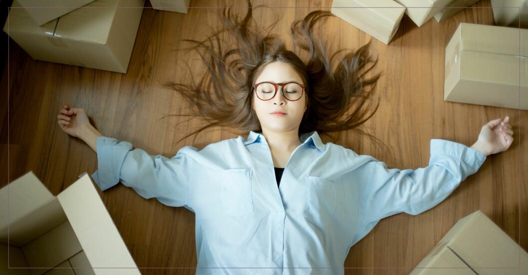 Ung kvinna ligger och blundar på golvet med kartonger runtomkring sig