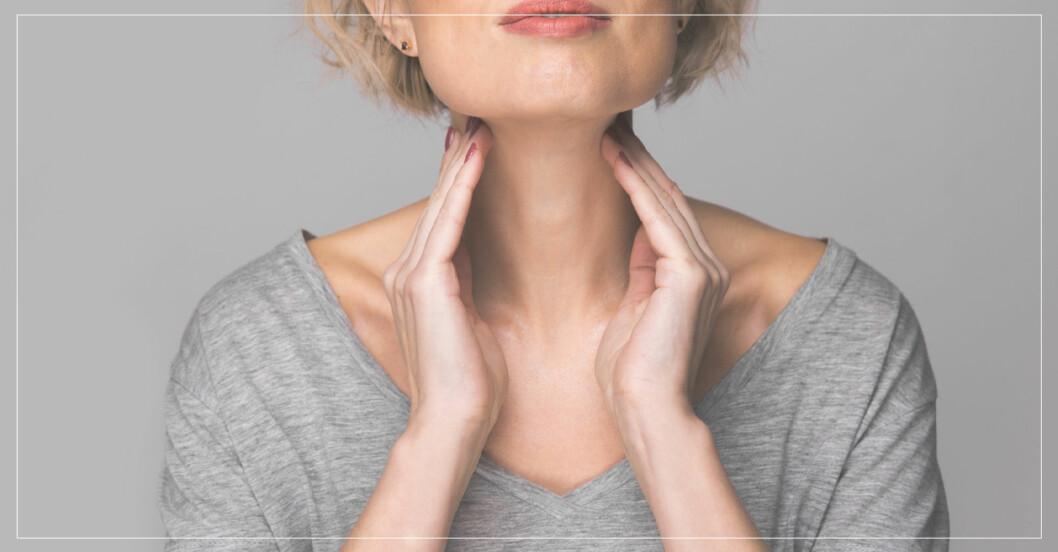 kvinna känner med händerna på sin hals