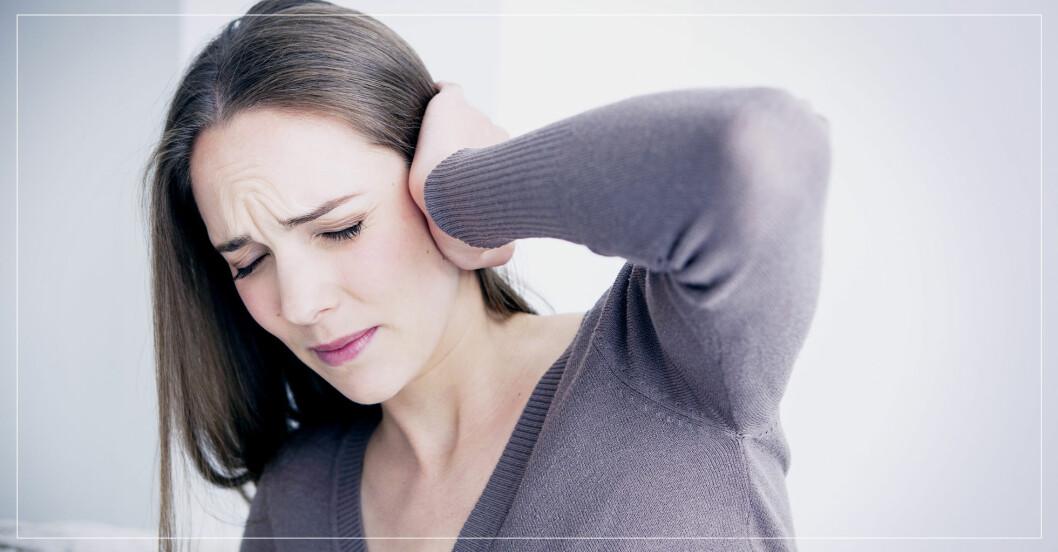 kvinna håller sig för örat och gör en grimas