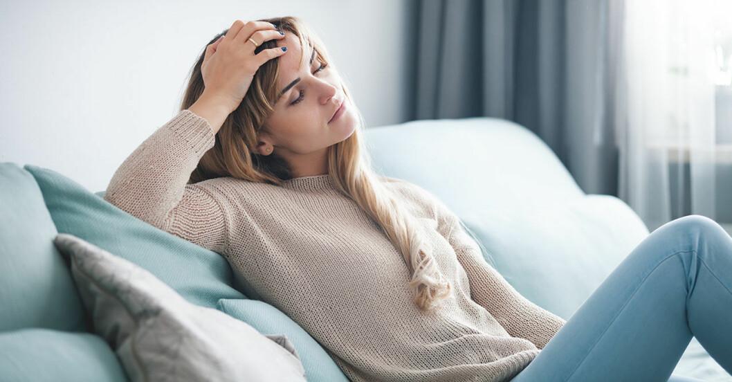 Trött kvinna sitter i soffan och tänker