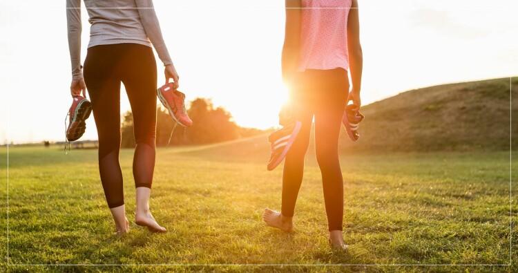 två kvinnor som håller i sina träningsskor på ett gräsfält