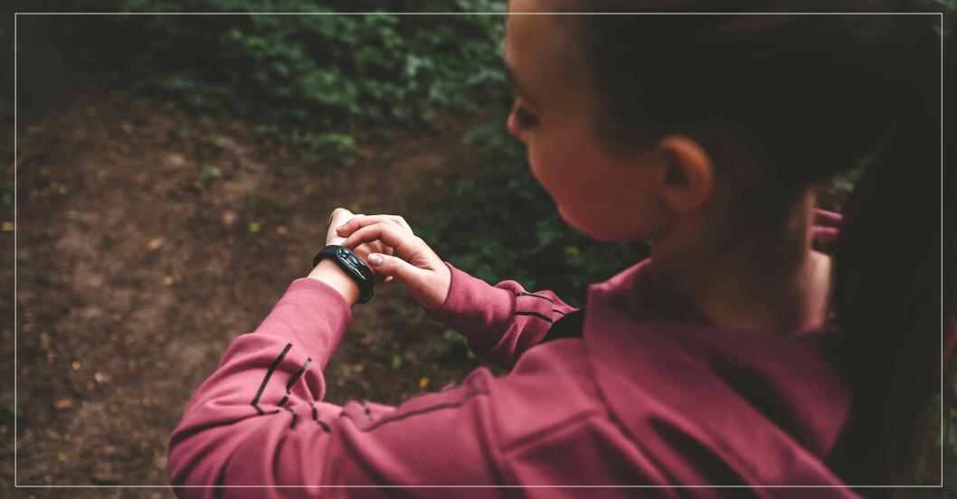 kvinna kollar sin klocka för att se hur många kalorier hon bränner på träningen