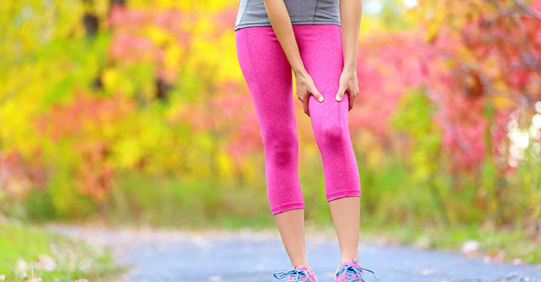 Kvinna i rosa tights har ont i benet.