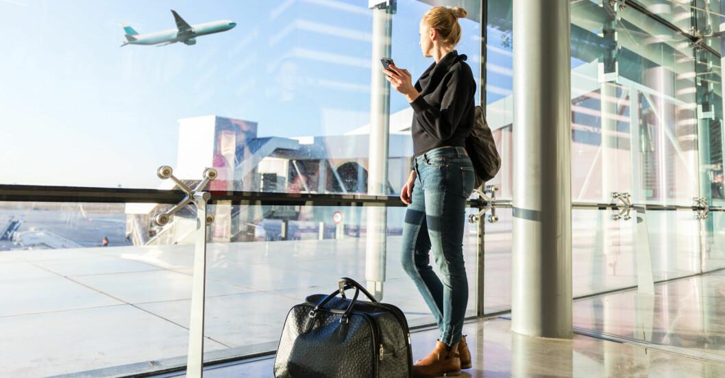 Kvinna står på flygplats ochtittar ut på ett plan som lyfter