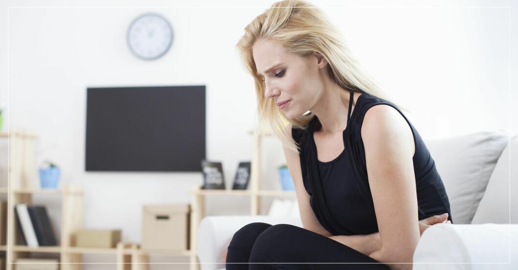 kvinna sitter i soffan och har ont i magen