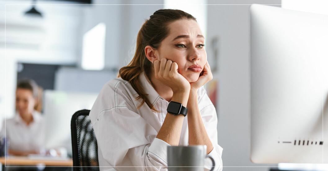Ung kvinna på jobbet tittar på datorskärmen och ser trött ut.