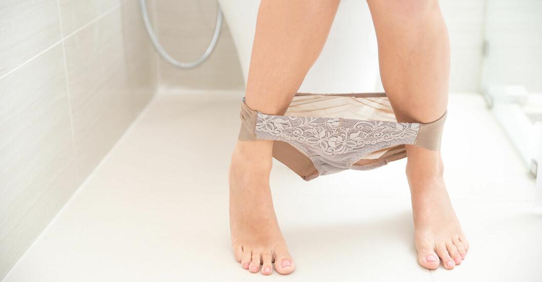 Kvinnoben med nedhasade spetstrosor i badrum.