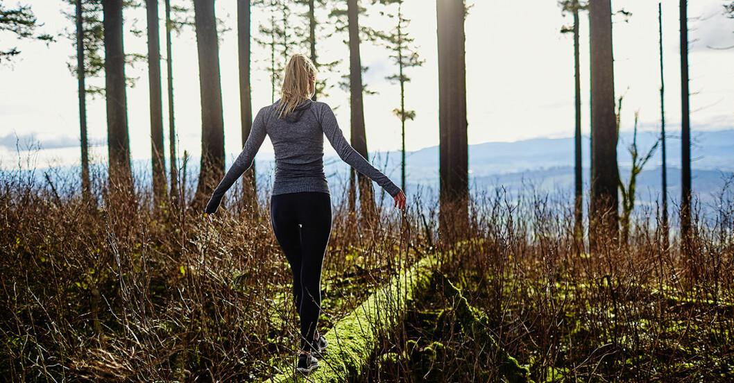 kvinna som går i skogen.